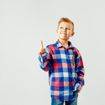 Junge, der buntes kariertes hemd, blue jeans, zeigend oben lokalisiert trägt. copyspase. lächeln.