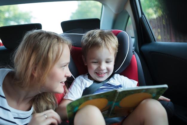 Junge, der das buch sitzt in einem auto mit mutter hält