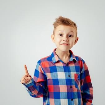Junge, der das bunte karierte hemd, zeigend oben lokalisiert trägt. copyspase. lächeln.