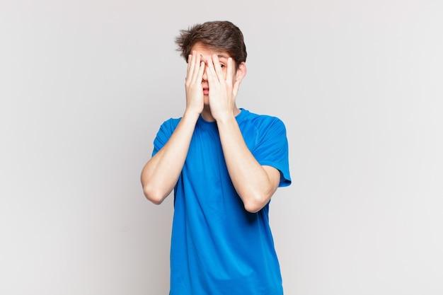 Junge, der das gesicht mit den händen bedeckt, mit überraschtem ausdruck zwischen den fingern späht und zur seite schaut