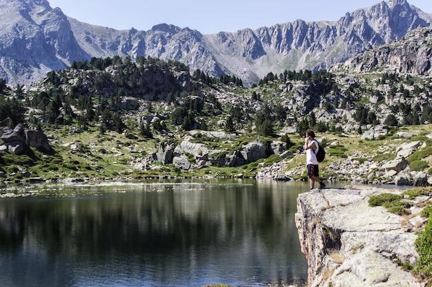 Junge, der das spiegelbild der berge im see betrachtet.