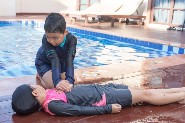 Junge, der dem ertrinken des kindermädchens im swimmingpool hilft, indem es cpr tut.
