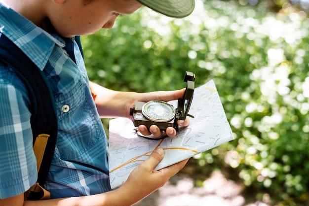 Junge, der den anweisungen eines kompasses folgt