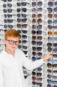 Junge, der die brillen betrachten kamera im optica wählt