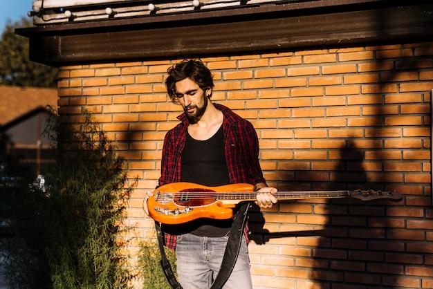 Junge, der die e-gitarre vor backsteinmauer hält