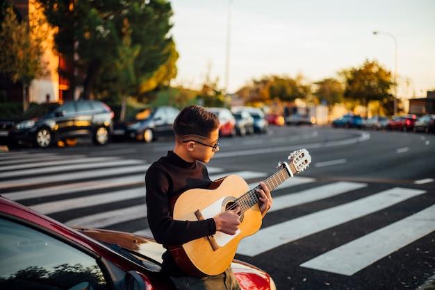 Junge, der die gitarre durch die stadt von madrid, spanien spielt.