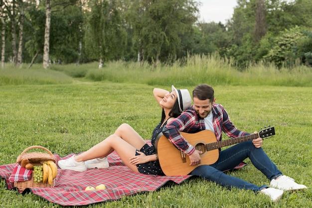 Junge, der die gitarre für seine freundin auf einer picknickdecke spielt