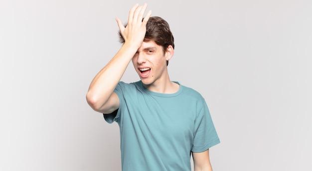 Junge, der die handfläche zur stirn hebt und denkt, oops, nachdem er einen dummen fehler gemacht oder sich erinnert hat, sich dumm zu fühlen?