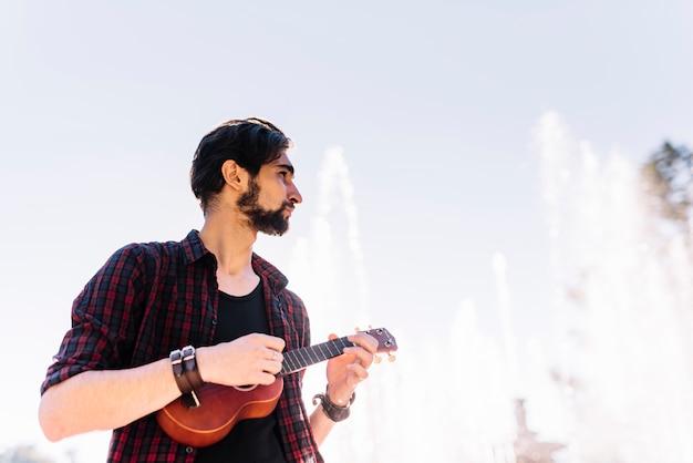 Junge, der die ukulele spielt