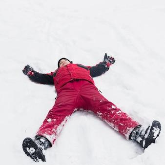 Junge, der die warme kleidung liegt auf schneebedeckter landschaft am wintertag trägt