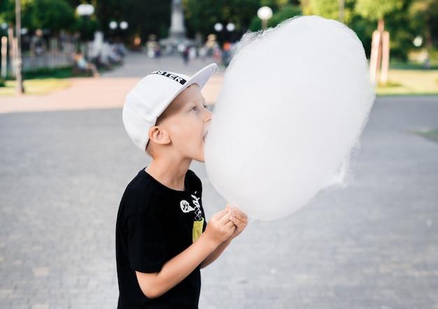 Junge, der die zuckerwatte gemacht vom klebrigen gesponnenen zucker steht im park isst