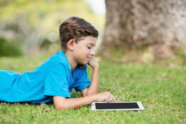 Junge, der digitale tablette im park verwendet
