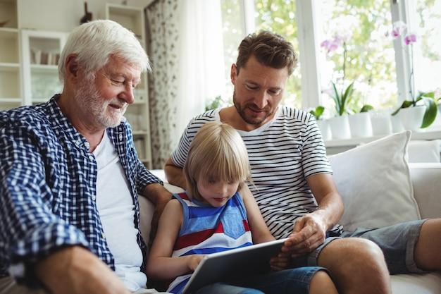 Junge, der digitales tablett mit seinem vater und großvater im wohnzimmer benutzt