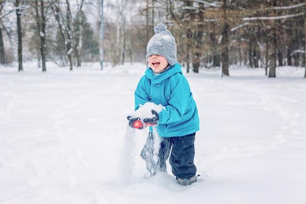 Junge, der draußen im schnee im winter spielt