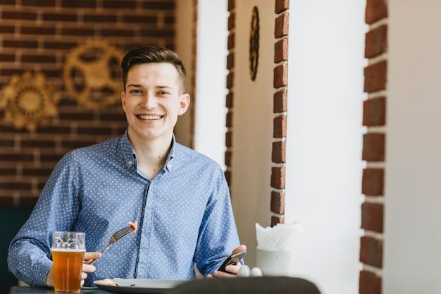 Junge, der ein bier in einem restaurant isst
