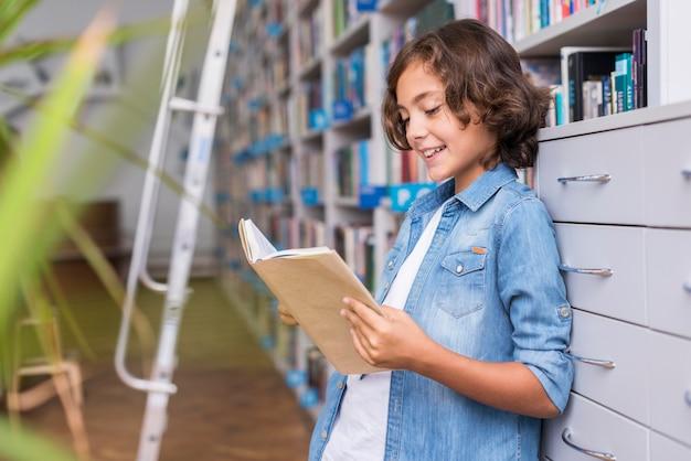 Junge, der ein buch in der bibliothek liest