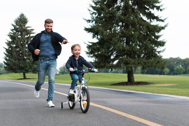 Junge, der ein fahrrad im park neben seinem vater fährt