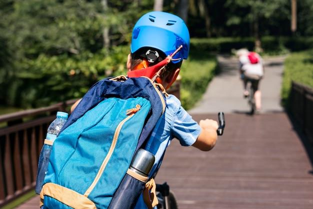 Junge, der ein fahrrad im park reitet
