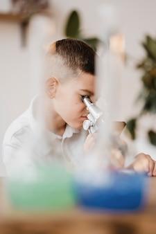 Junge, der ein mikroskop benutzt, um wissenschaft zu lernen