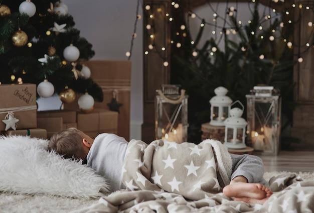 Junge, der ein nickerchen neben weihnachtsbaum macht