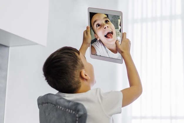Junge, der ein selbstporträt auf digitalem tablett nimmt
