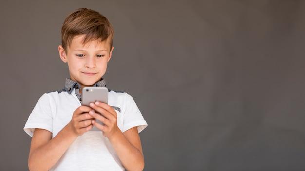 Junge, der ein spiel am telefon mit kopienraum spielt