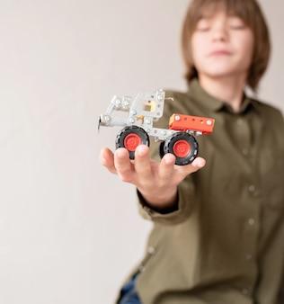 Junge, der ein spielzeugauto in seiner hand hält