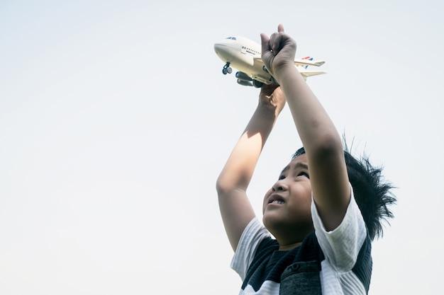 Junge, der ein spielzeugflugzeug im himmel fliegt