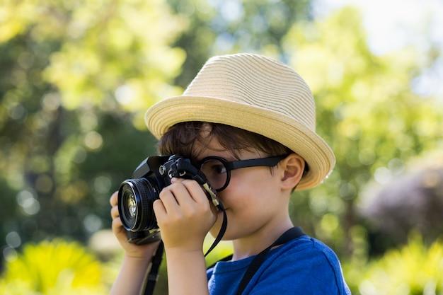 Junge, der eine fotografie von der kamera anklickt