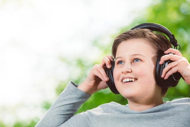 Junge, der eine musik durch riesige kopfhörer im außenwald hört