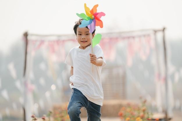 Junge, der eine spielzeugwindmühle hält, die glücklich im park läuft
