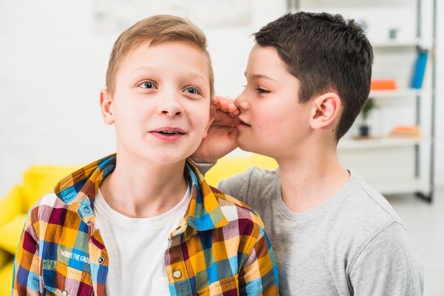 Junge, der einem freund sein geheimnis erzählt