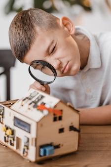 Junge, der einen elektrischen holzgegenstand mit einer lupe betrachtet