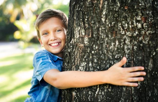 Junge, der einen großen baum im park umarmt