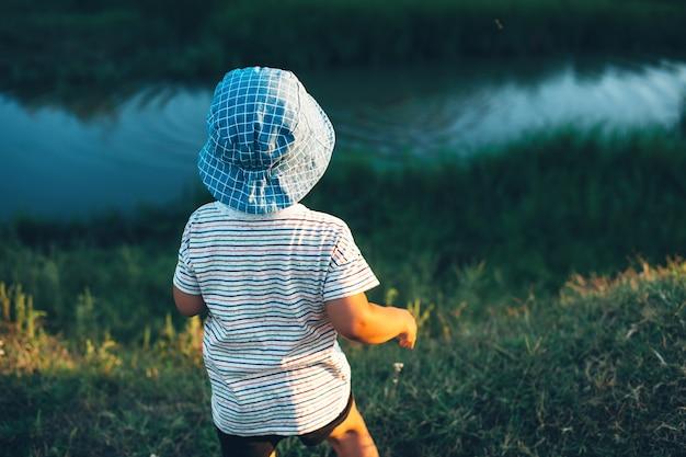 Junge, der einen kleinen fluss betrachtet und steine wirft, die einen blauen hut in einem grünen feld tragen