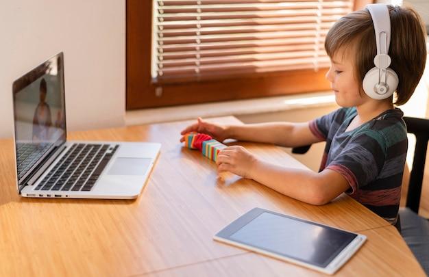 Junge, der einige spielzeuge auf online-klassen arrangiert