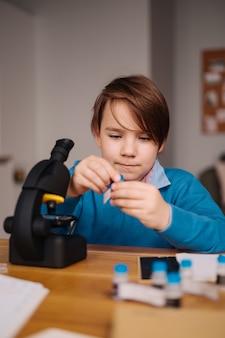 Junge der ersten klasse, der zu hause unter verwendung des mikroskops studiert