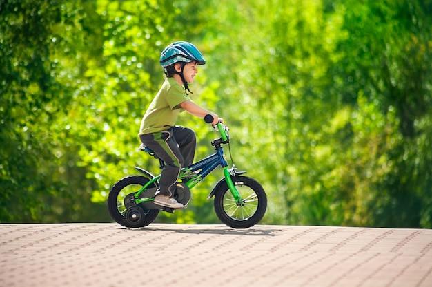 Junge, der fahrrad in einem helm reitet