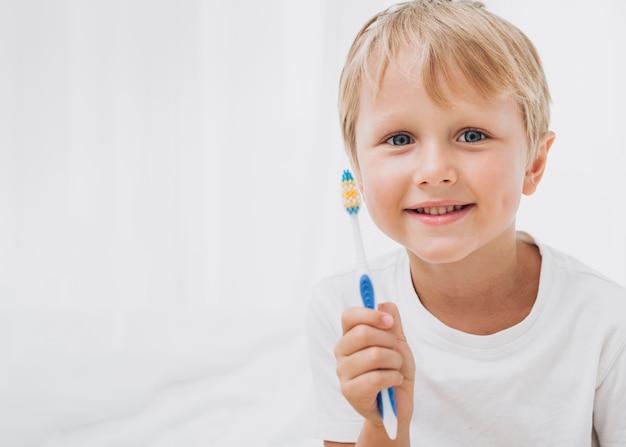 Junge, der fertig wird, seine zähne mit kopienraum zu putzen