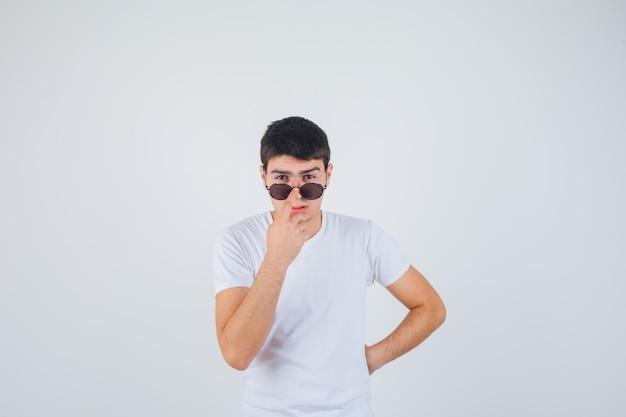 Junge, der finger auf brille im t-shirt hält und cool schaut. vorderansicht.