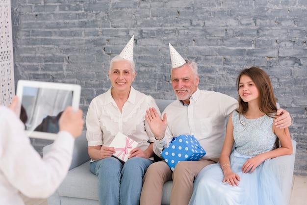 Junge, der foto seiner großeltern und schwester sitzt auf sofa mit digitaler tablette macht