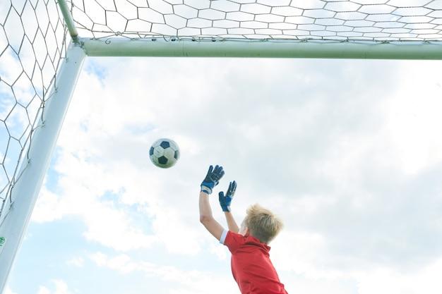Junge, der fußballtor verteidigt