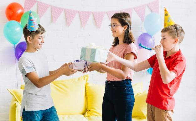 Junge, der geburtstagsgeschenk von seinen freunden empfängt
