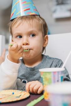 Junge, der geburtstagskuchen isst