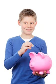 Junge, der geld in einem sparschwein spart