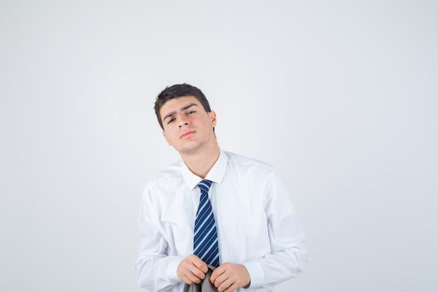 Junge, der gerade steht und an der kamera in weißem hemd, krawatte und gut aussehend, vorderansicht aufwirft.