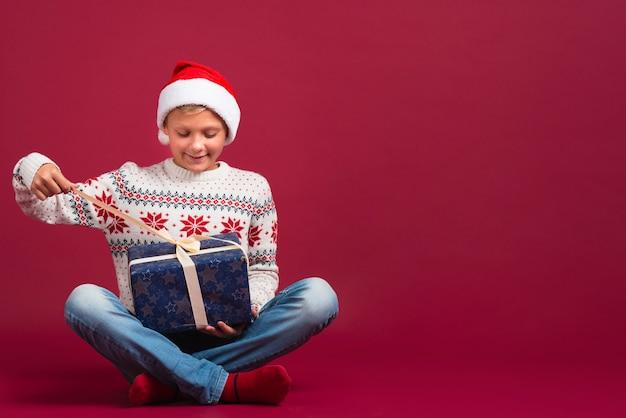 Junge, der geschenk mit kopienraum hält
