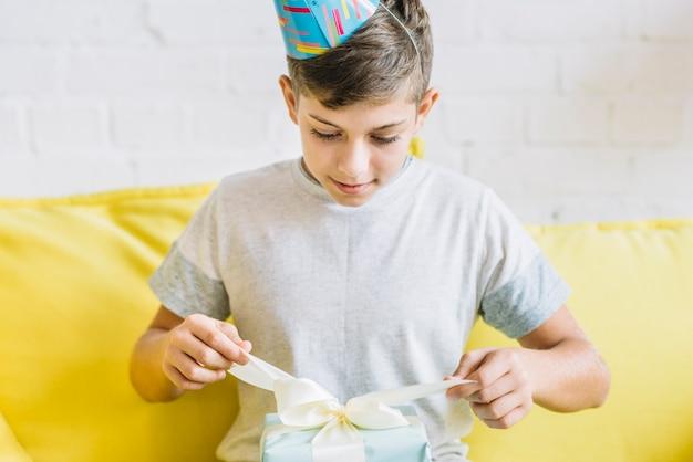 Junge, der geschenk während seines geburtstages auspackt