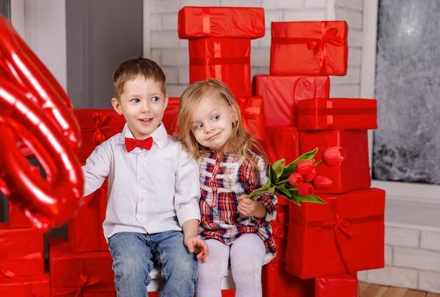 Junge, der geschenk zum kleinen mädchen im valentinstag des lässigen kleides präsentiert