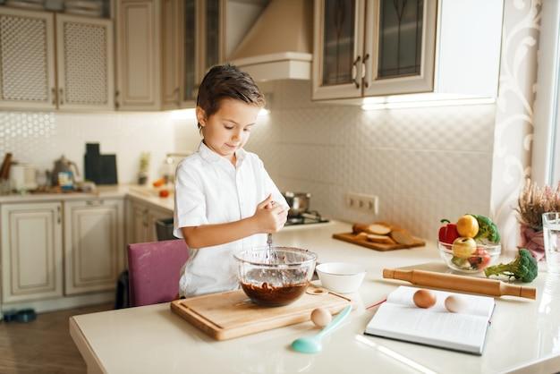 Junge, der geschmolzene schokolade in einer schüssel mischt.